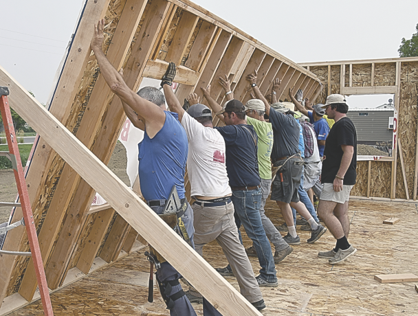 David Peck photo     A strong line of volunteer builders erects a finished wall at the new Water of Life Church building in Cowley Tuesday afternoon.  Some 29 volunteers journeyed to Cowley from Mississippi and four other states as part of the Church Building Ministries organization.