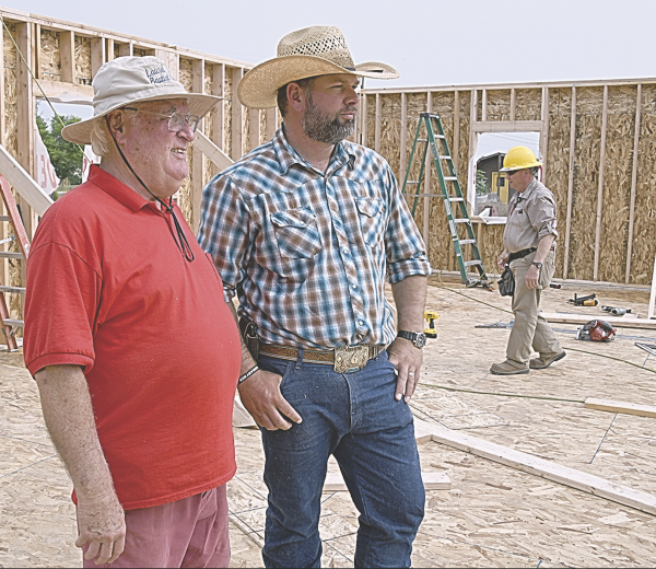 David Peck photo    Church Building Ministries, Inc. team leader Jack Honea (left) and Water of Life Church pastor Johannes Slabbert supervise construction work at the new church building in Cowley Tuesday. The team has been in Cowley for most of a week.