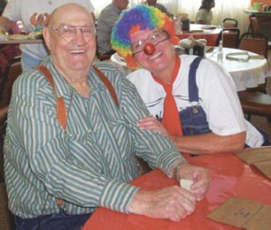 Pete Dykes enjoys a moment with clown Denise Andersen at the carnival held at the Big Horn County Senior Citizens Center on Aug. 24.