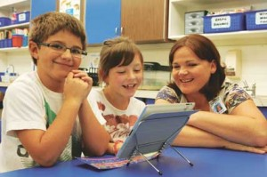 Dallen Mangus, Hailey Rael and teacher Jodi Strom work with one of the new iPads Lovell Elementary students are using as part of their educational program in the second grade classroom. Patti Carpenter photo