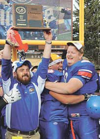 Coach Doug Hazen and seniors AJ Montanez and Garrett Angell celebrate after receiving the state championship trophy in the end zone following Lovell's 21-13 win over Lyman in the Class 2A championship game Friday afternoon at War Memorial Stadium in Laramie.