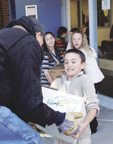 Jim Minchow helps student Brenden Lundberg load up non-perishable items collected by the students at Lovell Elementary School for the firemens' food baskets last Christmas, while students Natalia Jolley and Trecelle Jolley wait for their turn to load items.
