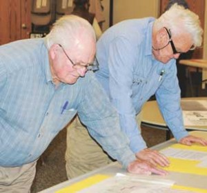 Gerald Brinkerhoff and Roger Hiser pore over material during the community open house Thursday night at the Lovell Community Center. Some 40 to 50 people attended the open house.