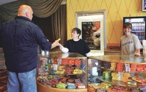 Chad Carr purchases a box of candy from volunteer Kathy Brown at the Hyart Theatre in Lovell as Jessica Carr, the only paid employee at the theatre, organizes candy on the shelves. The Hyart is kept afloat with the help of more than 100 volunteers. Patti Carpenter Photo