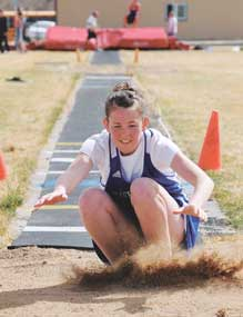 Lovell freshman Chayli McArthur kicks up a cloud of sand as she lands in the pit during a recent jumping event.