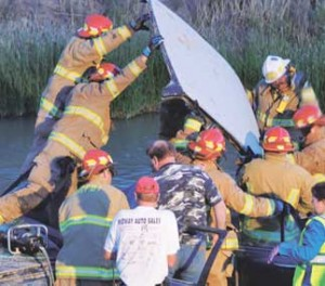 Lovell firemen remove the roof from a Buick sedan as part of the process to extricate Chris Day following his crash west of Byron on the banks of the Sidon Canal Sunday night.