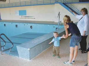 Dotty White, right, makes a point to Annabelle McCurley and her son Flint, age 2, during a visit to the former Byron school pool last week.
