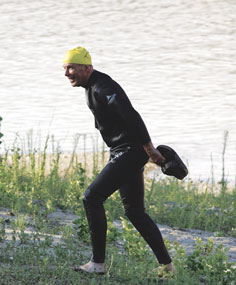 Roland Simmons grabs his shoes after the swim portion of the 2012 triathlon held at Horseshoe Bend on Saturday, July 7. Simmons, who is known for his positive attitude, challenges himself in the triathlon every year just for fun.