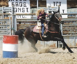 Dusty Willis of Deaver races around a barrel in the Junior Youth Barrel racing event at the Pioneer Day Rodeo held in Cowley on July 21.