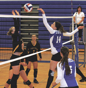Lady Bulldog Emilee Reasch tips the ball over the net, while Maddie Baxendale watches during a battle against the Shoshoni team at the North Big Horn County Tournament on Aug. 25.
