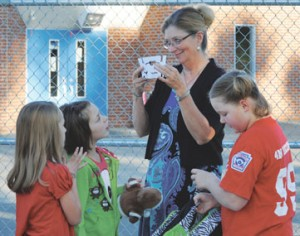 Lovell Elementary Principal Cheri Hoffman looks at a craft shown to her by Ashton Harper (left) and Alyssa Rael on the first day of school Tuesday. At the right is KayCee Twitchell.