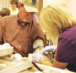 Kristi Schneider draws blood from Dennis Woodward at last year's Health Fair.