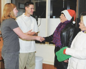 Kurt's Cuts owners Tammy and Kurt Wheeler greet Linda Martin and Karen Spragg during the Holiday Mingle in downtown Lovell on Saturday, Nov. 17.