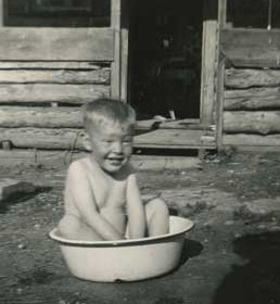 This baby picture of local author Grover Howe getting a bath in a metal tub shows the rustic conditions of the ranch he grew up on near Kane.