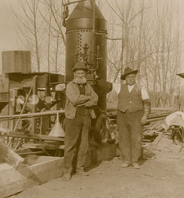Joseph Hyrum NeVille (right) stands with a family relative Jimmy Smith, in front of the outdoor flour mill he built and operated in Byron.