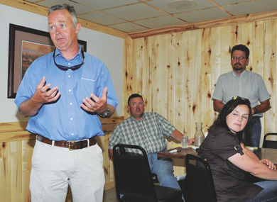 DOWL HKM engineer Andrew Mattie makes a point while WyDOT's Cody Beers and Keith Compson and DOWL HKM's Sarah Mainwaring look on during Monday's Main Street meeting at the Brandin' Iron. David Peck photo