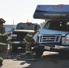 Lovell volunteer firemen inspect a damaged camper that was struck by the pickup shown here on Saturday evening at the Oasis Junction west of Lovell.