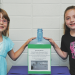 Natalie Hall (left) and Ashlee Pitt pose with the donations jar near the Lovell Elementary School office Tuesday. The two are leading a project to raise funds for schools damaged by flooding recently in Colorado. David Peck photo