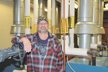 Longtime School District No. 2 Maintenance Director Ron Massine poses in the mechanical room at Lovell Middle School, a place with which the 32-year employee is intimately familiar. David Peck photo