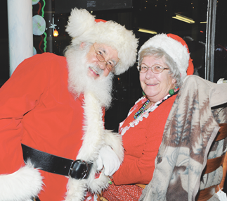 Mrs. Santa Claus (Judy Quarles), chats with her once-a-year husband, Santa, while sitting in the window of the Hen House during the 2012 Holiday Mingle. David Peck photo