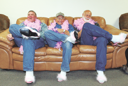 Rich Fink, Commissioner Keith Grant and Chad Petrich try to act as ladylike as possible in pink high heels and a feather boa, while supporting efforts to help victims of domestic violence in the county as part of a special awareness campaign launched by the CARES organization in October. Patti Carpenter photo