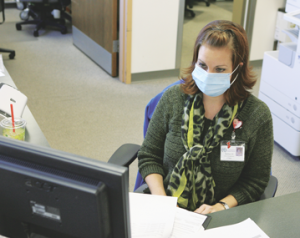 North Big Horn Hospital Clinic receptionist Barbara Mitchell models the type of mask that may, in some situations, provide the wearer with some protection from airborne droplets that may contain the flu virus.  Patti Carpenter photo