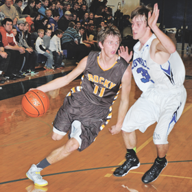 Rocky junior guard Bill Despain drives against Lovell defender Cade Bischoff during Rocky's 65-36 win Friday night in Lovell. The Grizzlies will travel to Thermop Friday while the Bulldogs host Greybull. David Peck photo