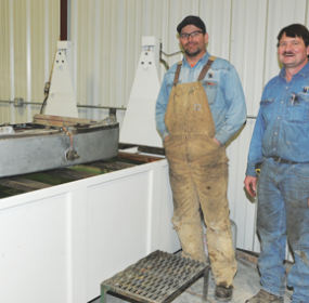 Levi Miller, left, and Scott Watson show off a test tank bearing a radiator ready to be tested at Miller's Fabrication Tuesday. Miller's Fabrication recently purchased Lovell Radiator from Phil Angell. David Peck photo