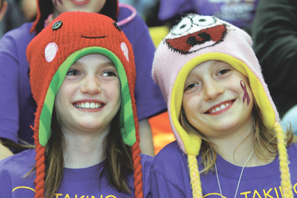 Victoria and Anna Arnold dress up in purple and cheer on their big sister Marissa during the Rocky girls varsity basketball game held in Cowley on Friday night. Patti Carpenter photo