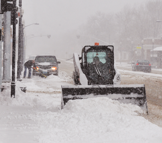 Town of Lovell employee Dan Beal clears snow on Lovell's Main Street Wednesday morning. Snow continued to fall all day.