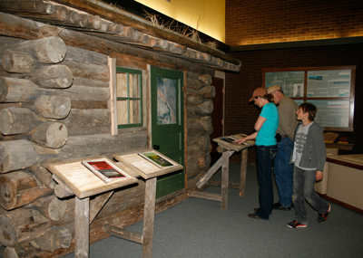 Rebecca and Aidan Searfoss of Hyattville and Wayne Bauer of Michigan look at a new display featuring historical ranches at the Bighorn National Park Service Visitors Center in Lovell. Bob Rodriguez