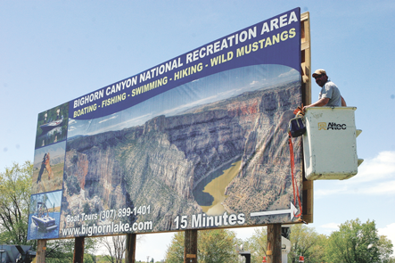 Paul Luthy of Chuck's Signs of Cody installs a new billboard on the east side of Lovell reminding locals and tourists to visit Big Horn Lake. Patti Carpenter photo