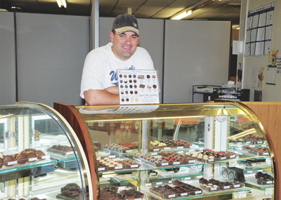 Jason Zeller poses in front of the display cases at the new Queen Bee Honey Candy storefront at 244 E. Main in Lovell. David Peck photo
