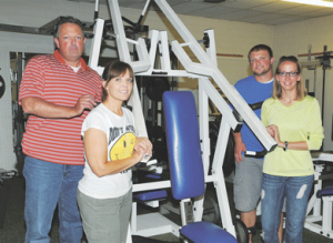 David Peck The Jameson family – (l-r) Mike, Cristy, Michael and Stormy – pose next to a piece of equipment at Better Body Fitness Monday. The family recently purchased the fitness center from Chad and Lindsay Lindsay, Kevin Walker and Jodi Lindsay.