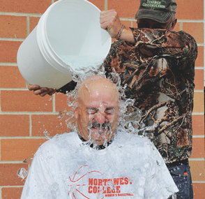 Lovell School Resource Officer and sheriff's deputy Steve Coleman gets a cold bucket of water over the head from Fire Dept. Capt. Bob Mangus last Friday morning at the fire hall.
