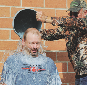 Lovell Fire Dept. Captain Bob Mangus dowses Big Horn County Emergency Management Coodinator Jason Beal with cold water for the ALS Challenge Friday morning at the fire hall in Lovell.