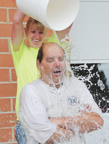 Leslie Blackburn looks quite pleased to be able to splash her father, Sheriff Ken Blackburn, with ice cold water as part of the ALS Challenge Friday morning at the Lovell Fire Hall.