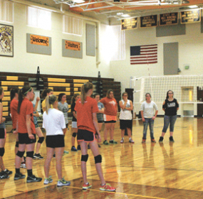 RMHS head coach Jamie Cooley and assistant coach Kayla Honeyman talk to a group of volleyball players at practice this week.