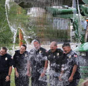 Several local law enforcement officers have accepted the ALS Challenge, raising money for the ALS Association. Here, a front-end loader dumps water on Lovell Police Dept. officers and dispatchers (l-r) Officer Jared Knudsen, Dispatcher Jennifer Massey, Chief Nick Lewis, Officer Kris Brimhall and Sgt. Noe Garcia. In the ALS Challenge, those challenged can accept the ice bucket challenge, make a donation to ALS or do both. Courtesy photo