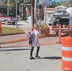 Lovell fourth-grader Kathryn Mickelson heads into the designated crossing zone on Shoshone Avenue in Lovell Tuesday afternoon as S&L Industrial employee and crossing guard Desaree Wimmler looks on. David Peck photo