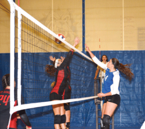 Senior Emilee Reasch sends a hit past Kemmerer's blockers Friday afternoon at the North Big Horn County Volleyball Tournament.
