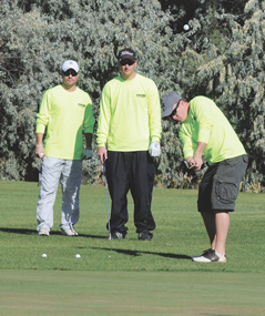 Nicholas Sponsel gets great height on a chip to the third hole green during the Friends of the Foundation Tournament Saturday as teammates Josh Sponsel and Eric Honeyman look on. The Cowley trio and Brock Frates of Byron took first place with their AMCOL Field team. David Peck photo