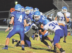 Lovell senior running back Cade Bischoff powers between a couple of Lyman tacklers during Lovell's 28-24 win Friday night at Robertson Stadium as Brandon Teter (4) and Zeke Collins (63) look on. The Bulldogs travel to Thermopolis Friday.