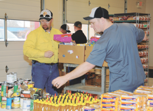 Firemen Justin Workman (left) and Jordan Hitz assemble Christmas food baskets at the Lovell Fire Hall on Monday. The firemen passed out 175 baskets this year. David Peck photo
