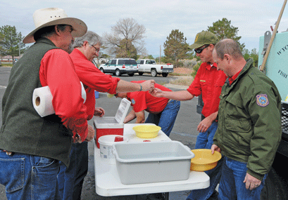The Wyoming Game and Fish cutthroat spawning crew -- (l-r) Pat Long, Steve Sharon, Bart Burningham, Steve Diekema and Guy Campbell – works to fertilize nearly 5,000 Yellowstone Cutthroat eggs during the mobile operation at the National Park Service parking lot east of Lovell on Tuesday morning. David Peck photo