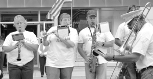 Longtime Mustang Band director Rick Parmer, right, plays trombone as he conducts the band during a pre-Follies street performance several years ago. Pictured are (l-r) Aletha Durtsche, Tanéa and Tyler Ennis and Parmer. File photo