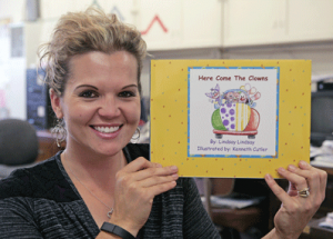 "Lovell Elementary School kindergarten teacher Lindsay Lindsay holds up a book she self-published entitled ""Here Come the Clowns."" Patti Carpenter photo"
