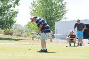Bruce Wolsey putts on the ninth green as teammates Kent Herren and Troy Butler look on Saturday afternoon during the Mustang Days golf tournament at Foster Gulch. David Peck photo