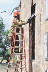 Doug Savage uses a stepladder to reach a hot spot at the shop fire west of Cowley Tuesday, one of more than 100 calls the fire department has already responded to this year. David Peck photo