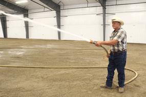 Fair board secretary Carl Nielson sprays down the new multi-pupose building floor at the Big Horn County Fairgrounds. Kynli Smith photo